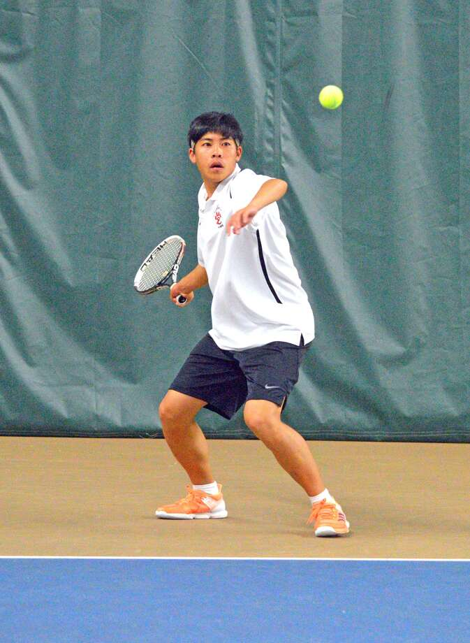 Edwardsville junior Jason Pan returns a shot during his No. 4 doubles match against Peoria Richwoods on Friday at the Meyer Center YMCA
