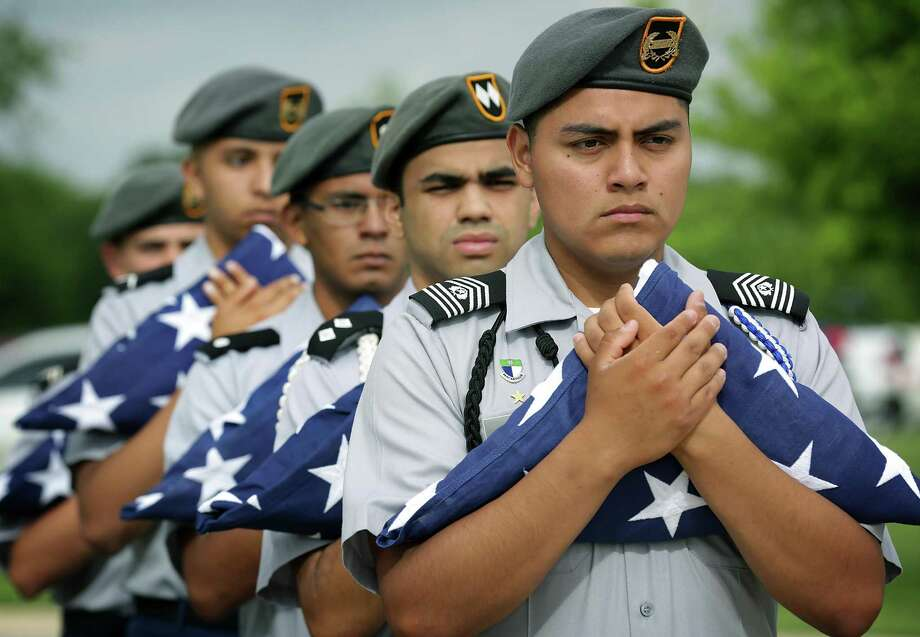 MacArthur High School JROTC members hold flags for veterans whose unclaimed remains were stored in the Amarillo area before they were interred at Fort Sam Houston National Cemetery. Photo: Photos By Bob Owen /San Antonio Express-News / ©2017 San Antonio Express-News