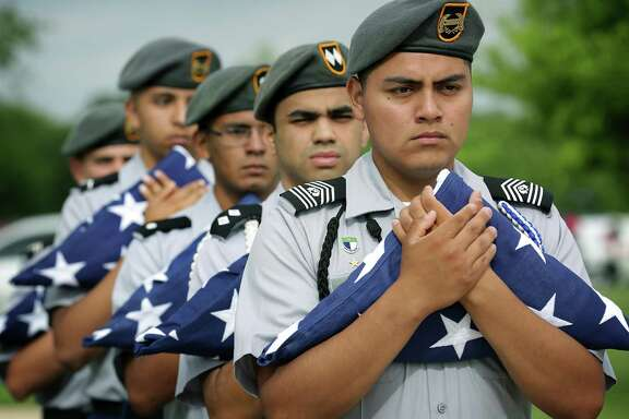 MacArthur High School JROTC members hold flags for veterans whose unclaimed remains were stored in the Amarillo area before they were interred at Fort Sam Houston National Cemetery.