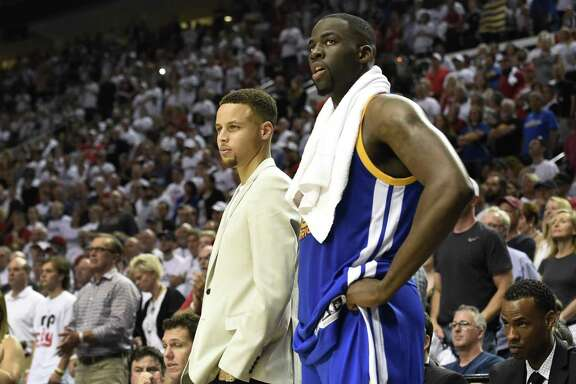 PORTLAND, OR - MAY 7: Stephen Curry and Draymond Green #23 of the Golden State Warriors look on from the bench as time winds down in the fourth quarter of Game Three of the Western Conference Semifinals during the 2016 NBA Playoffs at the Moda Center on May 7, 2016 in Portland, Oregon. The Blazers won 120-108. NOTE TO USER: User expressly acknowledges and agrees that by downloading and/or using this photograph, user is consenting to the terms and conditions of the Getty Images License Agreement.  (Photo by Steve Dykes/Getty Images)