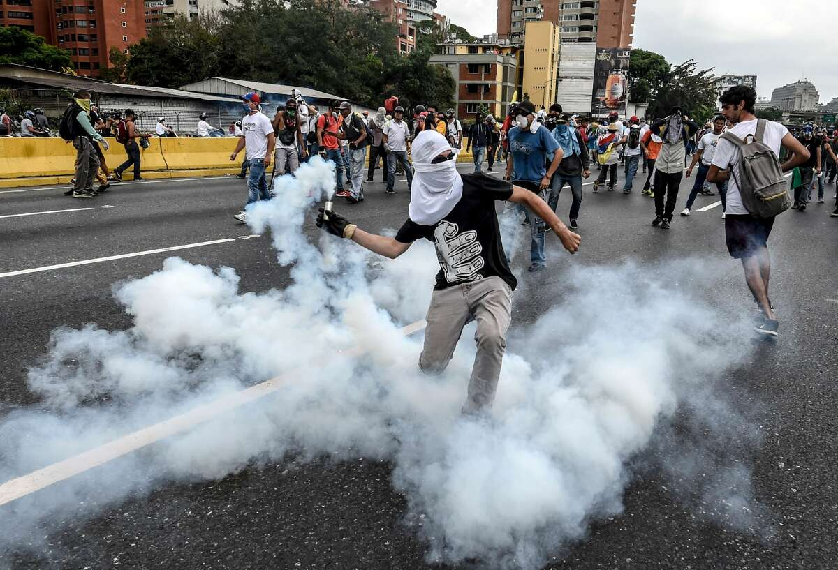 TOPSHOT - Demonstrators clash with the riot police during a protest against Venezuelan President Nicolas Maduro, in Caracas on April 20, 2017. Venezuelan riot police fired tear gas Thursday at groups of protesters seeking to oust President Nicolas Maduro, who have vowed new mass marches after a day of deadly unrest. Police in western Caracas broke up scores of opposition protesters trying to join a larger march, though there was no immediate repeat of Wednesday's violent clashes, which left three people dead. / AFP PHOTO / JUAN BARRETO (Photo credit should read JUAN BARRETO/AFP/Getty Images)