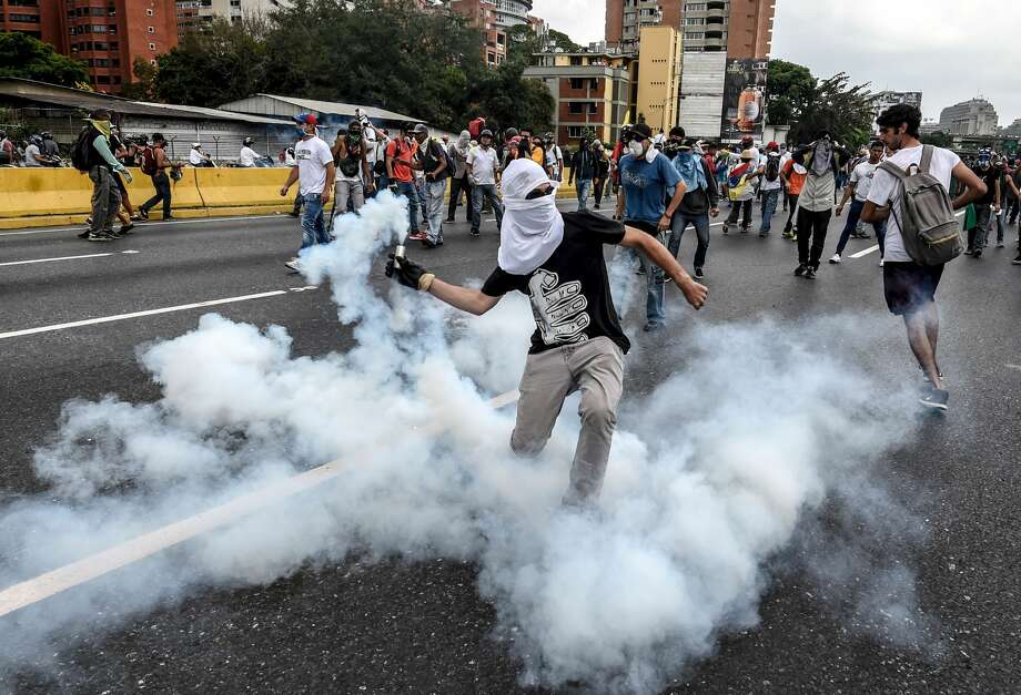 TOPSHOT - Demonstrators clash with the riot police during a protest against Venezuelan President Nicolas Maduro, in Caracas on April 20, 2017. Venezuelan riot police fired tear gas Thursday at groups of protesters seeking to oust President Nicolas Maduro, who have vowed new mass marches after a day of deadly unrest. Police in western Caracas broke up scores of opposition protesters trying to join a larger march, though there was no immediate repeat of Wednesday's violent clashes, which left three people dead. / AFP PHOTO / JUAN BARRETO        (Photo credit should read JUAN BARRETO/AFP/Getty Images) Photo: JUAN BARRETO/AFP/Getty Images