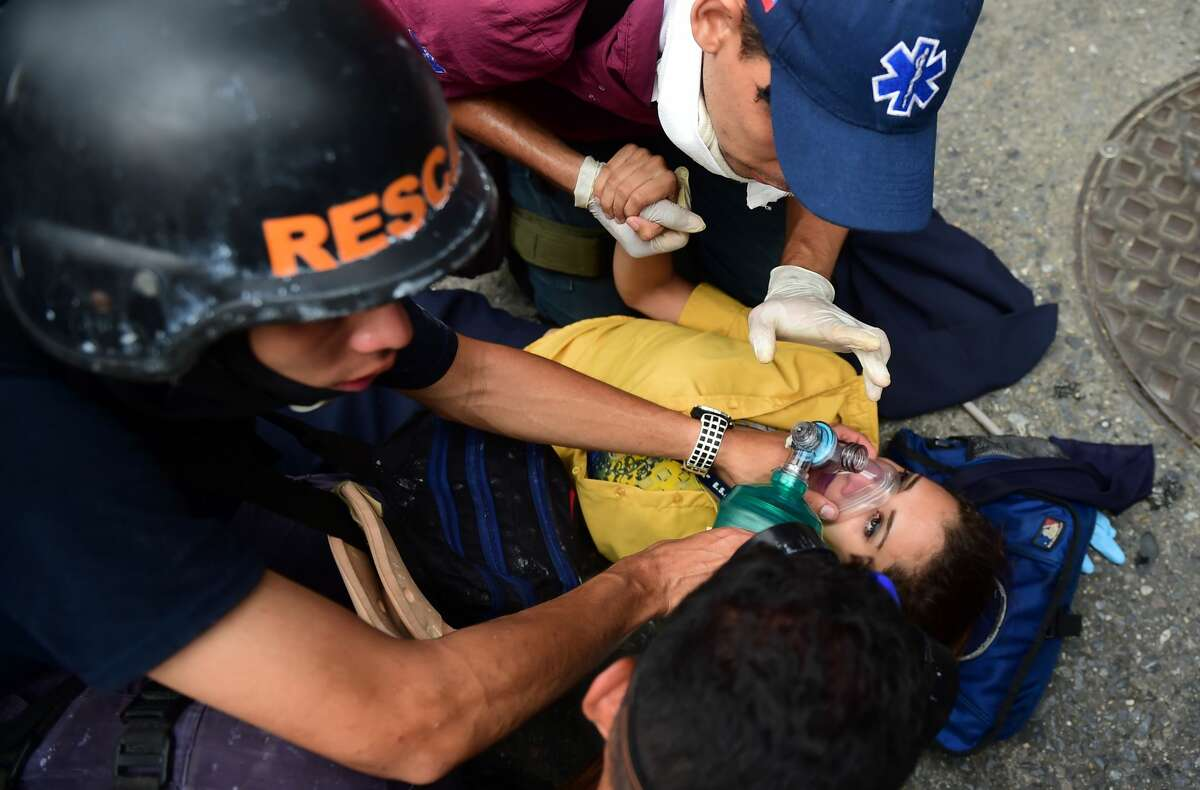 TOPSHOT - Rescue workers assist a woman after clashes with the riot police during a protest against Venezuelan President Nicolas Maduro, in Caracas on April 20, 2017. Venezuelan riot police fired tear gas Thursday at groups of protesters seeking to oust President Nicolas Maduro, who have vowed new mass marches after a day of deadly unrest. Police in western Caracas broke up scores of opposition protesters trying to join a larger march, though there was no immediate repeat of Wednesday's violent clashes, which left three people dead. / AFP PHOTO / RONALDO SCHEMIDT (Photo credit should read RONALDO SCHEMIDT/AFP/Getty Images)