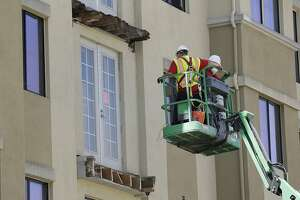 A crew work on the remaining wood of an apartment building balcony that collapsed, top, and one that was removed, below, in Berkeley, Calif., Thursday, June 18, 2015. A balcony broke loose from an apartment building during a 21st birthday party early Tuesday, killing several and seriously injuring several others. (AP Photo/Jeff Chiu)