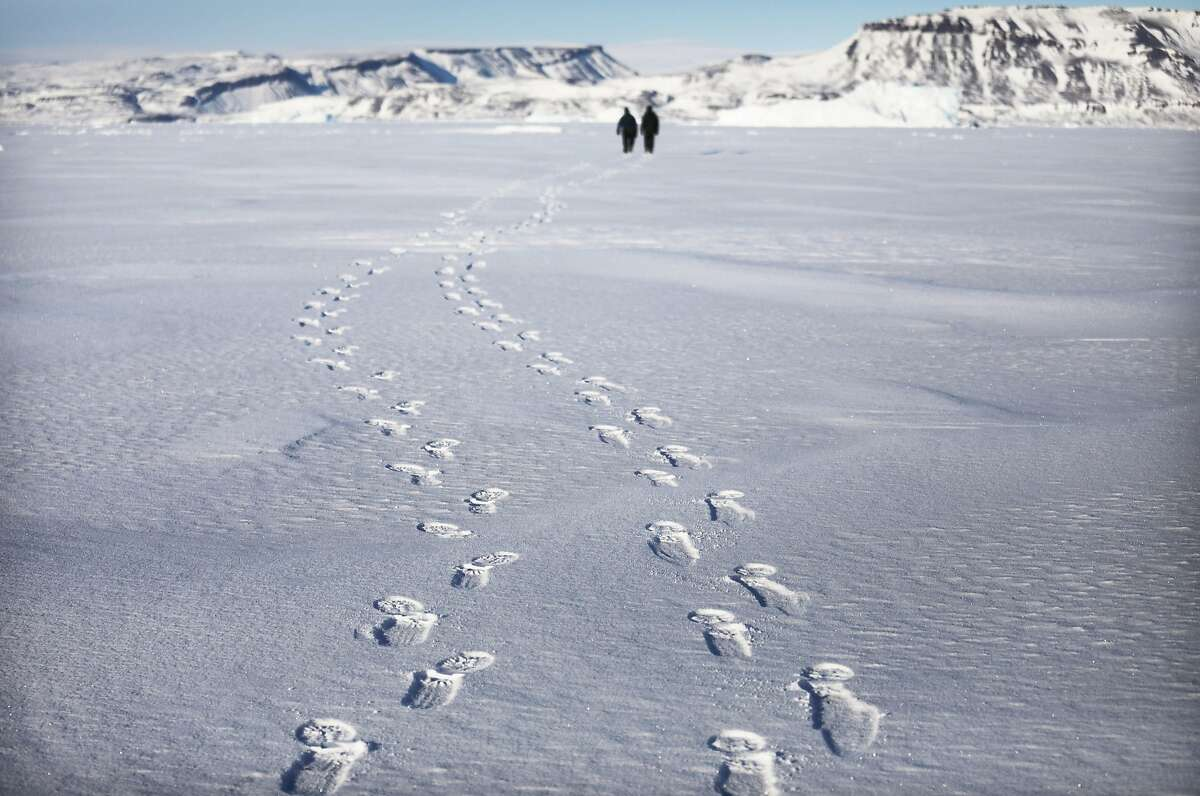 PITUFFIK, GREENLAND - MARCH 26: Project scientist Nathan Kurtz and senior support scientist Jeremy Harbeck walk on their way to survey an iceberg locked in sea ice near Thule Air Base on March 26, 2017 in Pituffik, Greenland. NASA's Operation IceBridge is flying research missions out of Thule Air Base and other Arctic locations during their annual Arctic spring campaign. IceBridge team members took the rare opportunity to survey sea ice near the base from the ground. Thule Air Base is the U.S. military's northernmost base located some 750 miles above the Arctic Circle. NASA's Operation IceBridge has been studying how polar ice has evolved over the past nine years and is currently flying a set of eight-hour research flights over ice sheets and the Arctic Ocean to monitor Arctic ice loss aboard a retrofitted 1966 Lockheed P-3 aircraft. According to NASA scientists and the National Snow and Ice Data Center (NSIDC), sea ice in the Arctic appears to have reached its lowest maximum wintertime extent ever recorded on March 7. Scientists have said the Arctic has been one of the regions hardest hit by climate change. (Photo by Mario Tama/Getty Images)