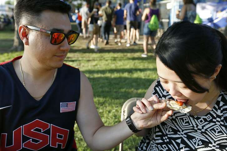 Richard Holtrop and Sherlyn Gan enjoy baked oysters during the 2017 Fiesta Oyster Bake held Friday April 21, 2017 on the St. MaryÕs University campus.