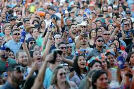With smartphones and Bud Lights raised high, a crowd cheers a Fiesta Oyster Bake performance.