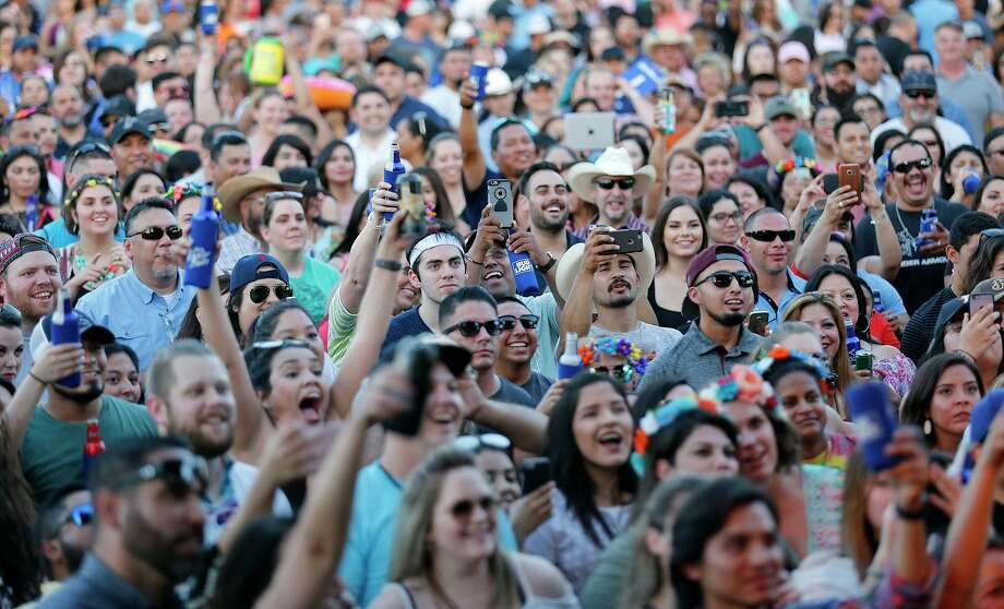 With smartphones and Bud Lights raised high, a crowd cheers a Fiesta Oyster Bake performance. Photo: Staff File Photo / © 2017 San Antonio Express-News