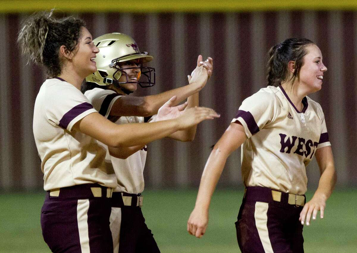 Magnolia West's Lauren Corley, right, jokes with Ariana Adams and Lauren Martinez after defeating Huntsville 10-0 in five innings to clinch a share of the District 20-5A softball title, Friday, April 21, 2017, in Magnolia.