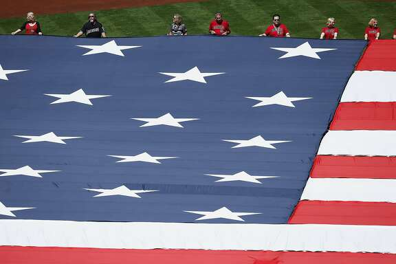 Arizona Diamondbacks fans hold the American flag for the national anthem prior to an Opening Day baseball game between the Diamondbacks and the San Francisco Giants Sunday, April 2, 2017, in Phoenix. (AP Photo/Ross D. Franklin)