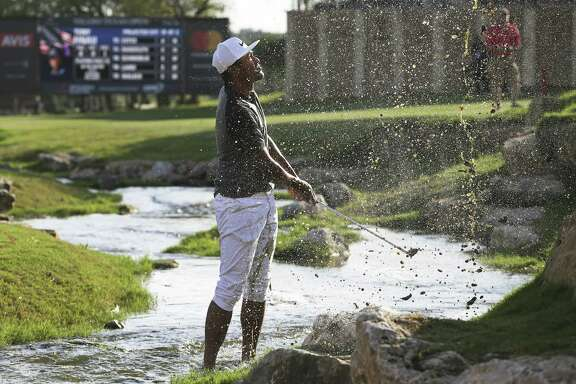 Tony Finau sprays muddy water on himself getting his ball up to the 18th green where he missed the par save and fell into a tie for the lead at 8 under during the second round of the Valero Texas Open at TPC San Antonio Oaks Course on April 21, 2017.