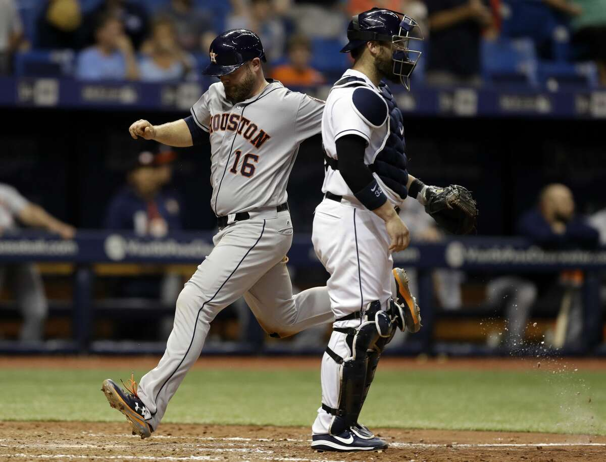 Houston Astros' Brian McCann (16) scores past Tampa Bay Rays catcher Derek Norris on a sacrifice fly by Josh Reddick during the ninth inning of a baseball game Friday, April 21, 2017, in St. Petersburg, Fla. (AP Photo/Chris O'Meara)