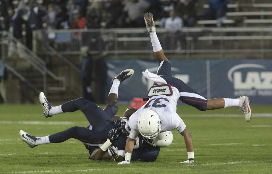 UConn WR Keyion Dixon is tackled as defender John Robinson (31) goes over the top during the first half of Friday's scrimmage. Photo: Michael McAndrews / Associated Press / Hartford Courant