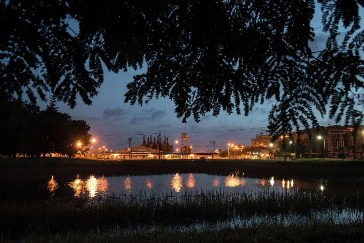 The sky at dusk is cut by the orange glow of the shuttered refinery at the Paranam Operations of Suralco, a subsidiary of Alcoa, on Saturday, March 11, 2017 in Suriname. The plant is now idle. (Stephanie Strasburg/Post-Gazette)