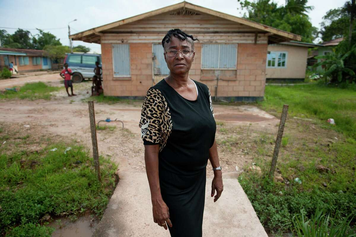 Gladys Renfurm, an elementary school teacher, stands above pooled water tainted with sewage in her neighborhood in Moengo, Suriname on Friday, March 10, 2017. ?'If it has rained, you can?•t breathe.?
