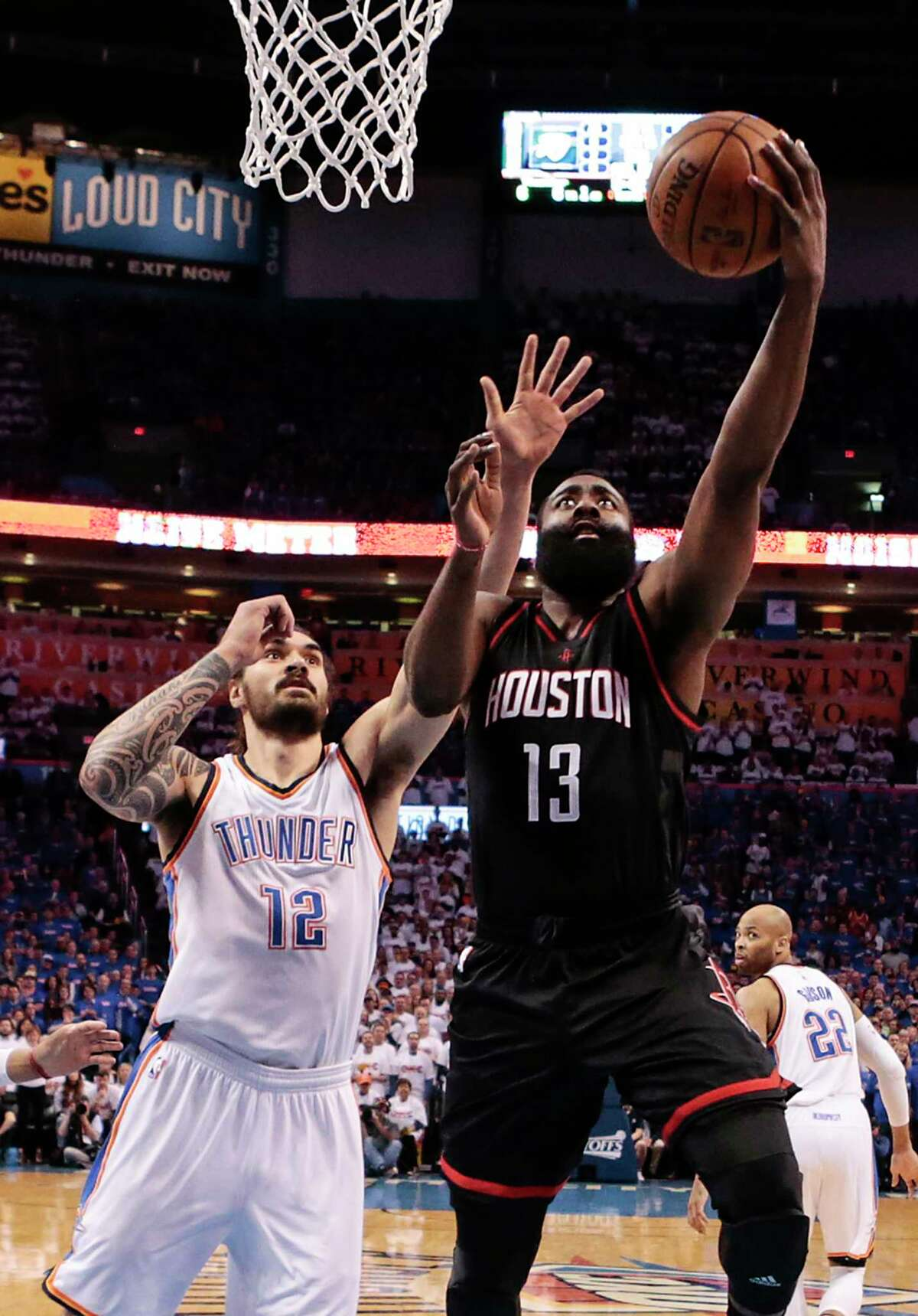 Houston Rockets guard James Harden (13) shoots a layup as he runs past Oklahoma City Thunder center Steven Adams (12) during the first half of Game 3 of the NBA Western Conference first-round playoff series at Chesapeake Energy Arena on Friday, April 21, 2017, in Oklahoma City. ( Brett Coomer / Houston Chronicle )