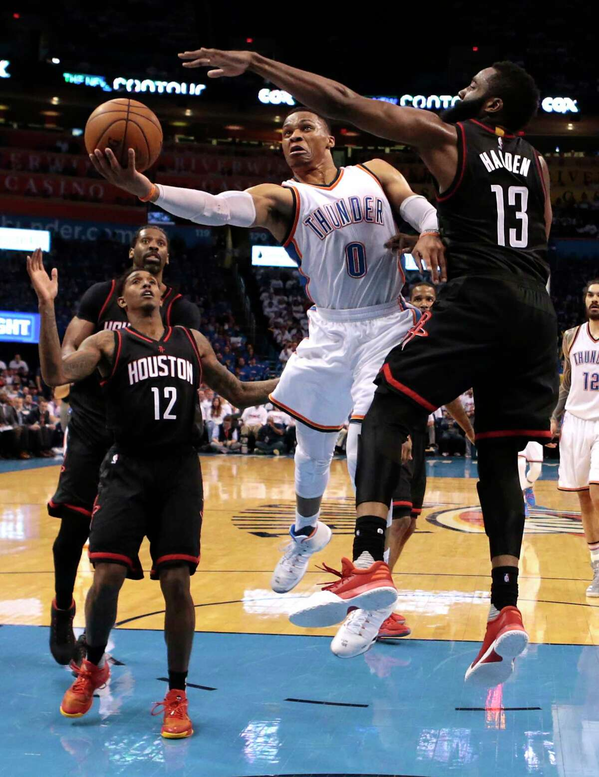 Russell Westbrook (0) got the best of James Harden on this second-half drive, and the Thunder capitalized on Harden's miss at the buzzer to hang on for the win and halve the Rockets' series lead.