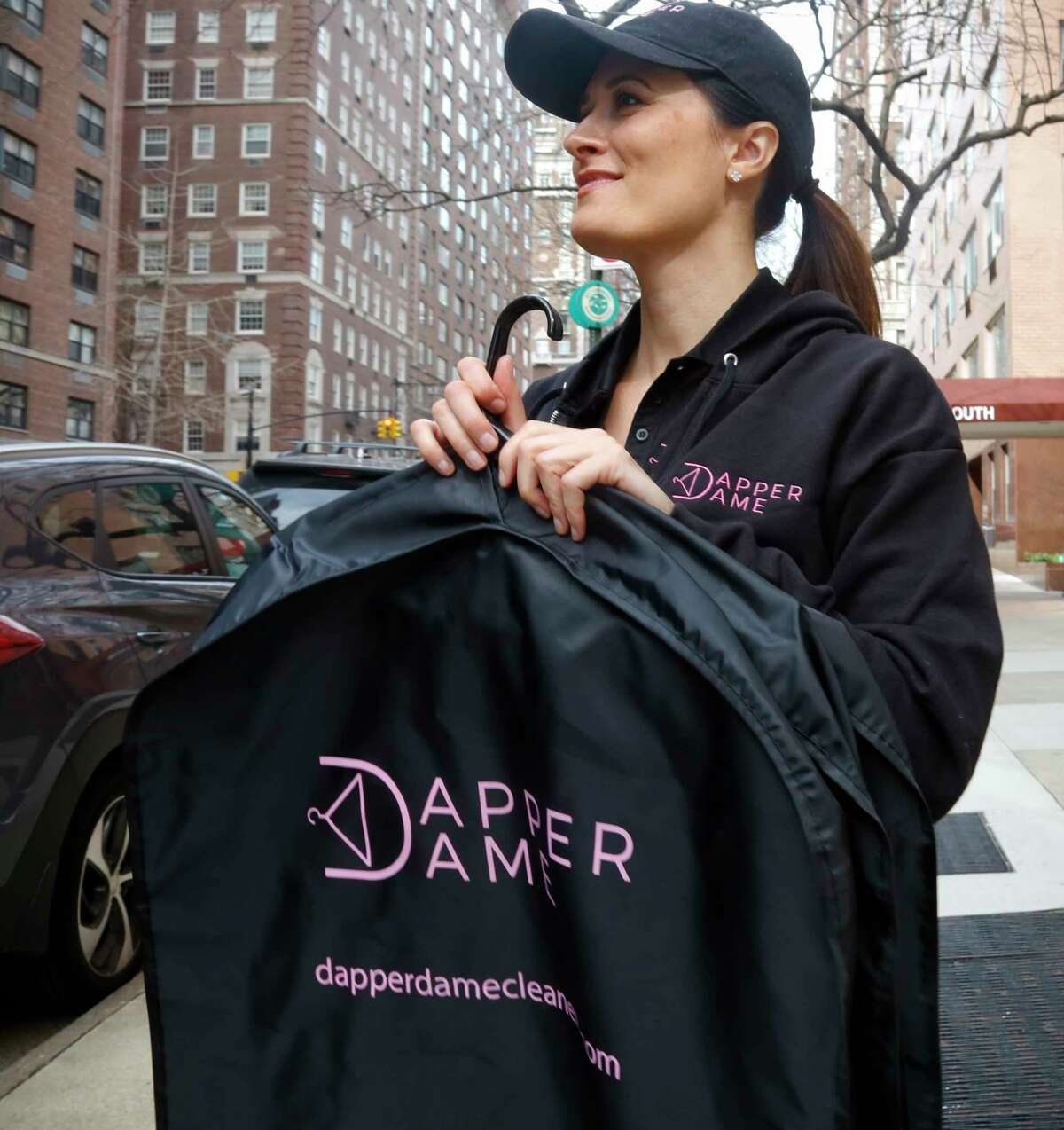In this Tuesday, April 11, 2017, photo, Reilly Starr, founder and president of Dapper Dame, a dry cleaning and laundry business, poses for a picture at Manhattan's Sutton Place, near where some of her clients live, in New York. Starr launched in early 2017 without a storefront; using an app to connect with customers and contracting with a wholesale dry cleaning company to do the work. (AP Photo/Bebeto Matthews)