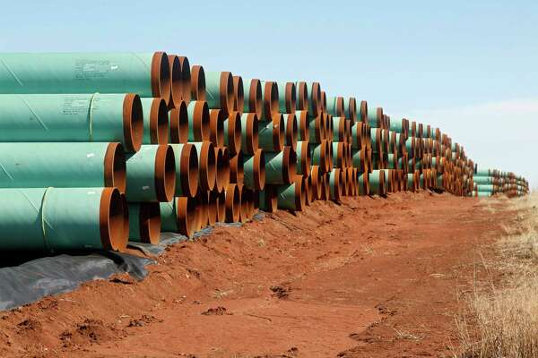 """FILE - In this Feb. 1, 2012 file photo, miles of pipe ready to become part of the Keystone Pipeline are stacked in a field near Ripley, Okla. It was a nice story while it lasted. Moments from signing orders to advance the stalled Keystone XL and Dakota Access pipelines, President Donald Trump comes up with the idea of making the projects use pipes and steel made in the U.S. He inserts a """"little clause"""" to that effect and vows the projects will only happen if his buy-American mandate is met.  (AP Photo/Sue Ogrocki, File)"""