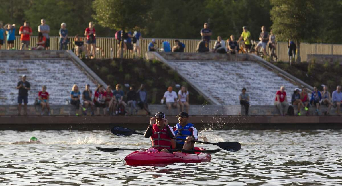 Support staff members watch from a kayak as triathletes compete in the swimming portion of the Ironman North American Championship, Saturday, April 22, 2017, in The Woodlands.