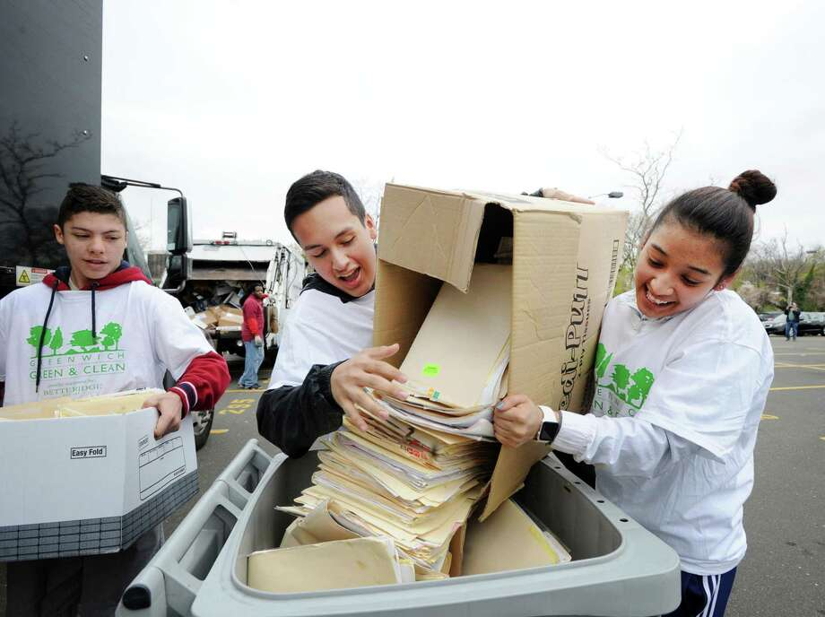 "Volunteers Nico Venegas, center, and Kathy Castellanos, right, dump a box full od paper into a shredding bin during the annual Paper Shredding Day in the Island Beach parking lot in Greenwich, Conn., Saturday, April 22, 2017.  According to Mary Hull, president of Greenwich Green & Clean, an organizer of the event along with the Greenwich Recycling Advisory Board, said ""Wow great turn out. Great Earth Day event. Lots of smiles for recycling."" The event was sponsored by First Bank of Greenwich and Santaguida Sanitation and was staffed with teenagers from the Boys and Girls Club and volunteers from various town organizations. Photo: Bob Luckey Jr. / Hearst Connecticut Media / Greenwich Time"
