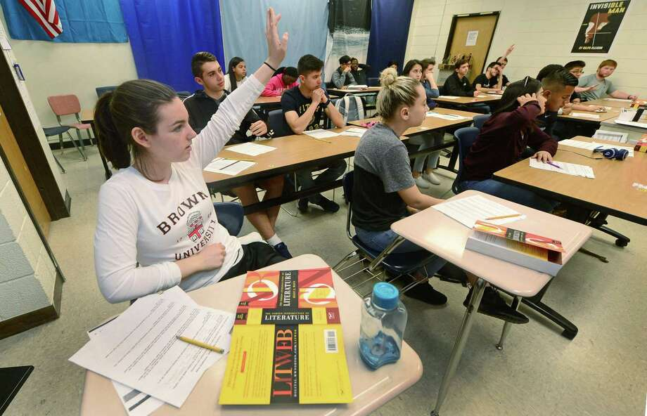 Norwalk High School Junior Erin Aymerich, left, looks to answer a question during her English 102: Literature and Composition class Tuesday, April 18, 2017, as part of The Norwalk Early College Academy, the states first P-TECH 9-14 school, which allows students to earn an associates degree in applied science at the high school in Norwalk, Conn. The program, which is a collaboration between Norwalk Public Schools, Norwalk Community College and IBM, will expand its capacity from 100 to 175 students for the upcoming school year thanks to additional magnet school funding slated to be approved in the school districts forthcoming 2017-18 operating budget. Photo: Erik Trautmann / Hearst Connecticut Media / Norwalk Hour