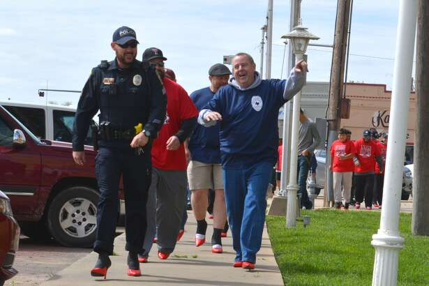 Walking a Mile Doug McDonough/Plainview Herald Plainview Police Chief Ken Coughlin points the way while leading the way Saturday during the fourth annual Walk a Mile in Her Shoes event. Held outside the Hale County Courthouse, the walk for men wearing high-heel pumps is designed to raise awareness about sexual assault and domestic violence while benefiting the Crisis Center of the Plains.