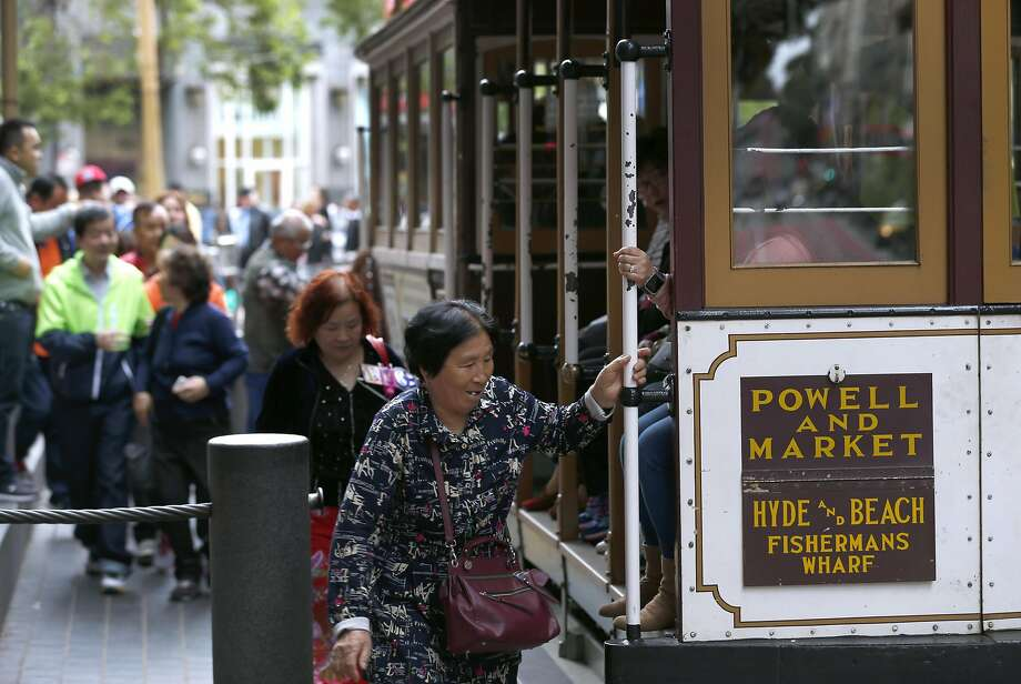 Passengers climb aboard a cable car at Powell and Market streets. Muni may eliminate cash fares on board the world famous cable cars after a brakeman was accused of stealing the fares. Photo: Paul Chinn, The Chronicle
