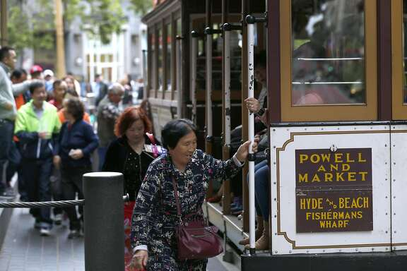 Passengers climb aboard a cable car at Powell and Market streets in San Francisco, Calif. on Saturday, April 22, 2017. Muni may eliminate cash fares on board the world famous cable cars after a brakeman was accused of stealing the fares.