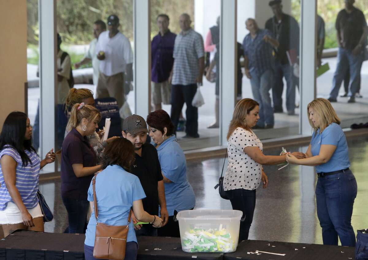 People recieve a wrist band as they enter Lakewood Church, 3700 Southwest Fwy., for the Make It Right! event Saturday, April 22, 2017, in Houston. The program offers thousands of people a chance to clear up pending cases, including open warrants, for certain Class C Misdemeanors arising from cases filed in Harris County Precinct 1 and Precinct 6. Approximately 5,000 letters were mailed to eligible persons to inform them of this opportunity. A career and educational fair and free legal advice from volunteer defense lawyers regarding landlord-tenant issues, immigration, child support and other areas was also offered to the public. ( Melissa Phillip / Houston Chronicle )
