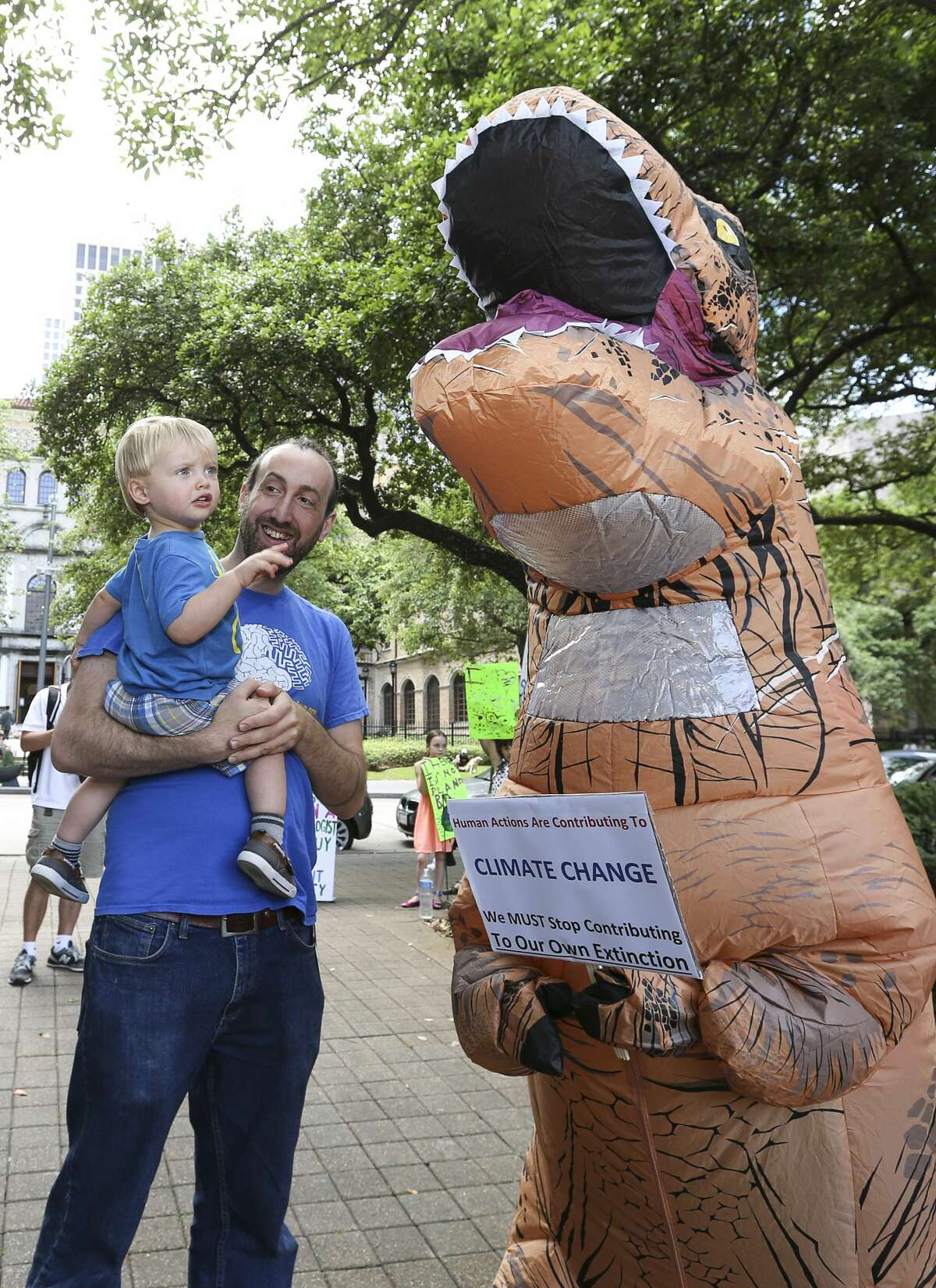 Jake Reimer, a neuroscientist at Baylor College of Medicine, takes his son, Silas, to meet a dressed-up Tyrannosaurus at the March for Science to support science Saturday, April 22, 2017, in Houston. The march began from Sam Houston Park and ended at City Hall. ( Yi-Chin Lee / Houston Chronicle )
