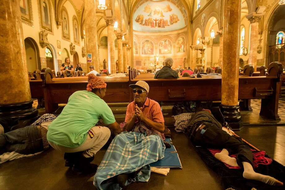 Porsha Dixson speaks with a homeless man at St. Boniface Catholic Church, where the Gubbio Project lets homeless people sleep in pews during the day, on Friday, April 21, 2017, in San Francisco. Dixson was nearby when William Ellis, a homeless man seeking shelter, collapsed and died. Photo: Noah Berger, Special To The Chronicle