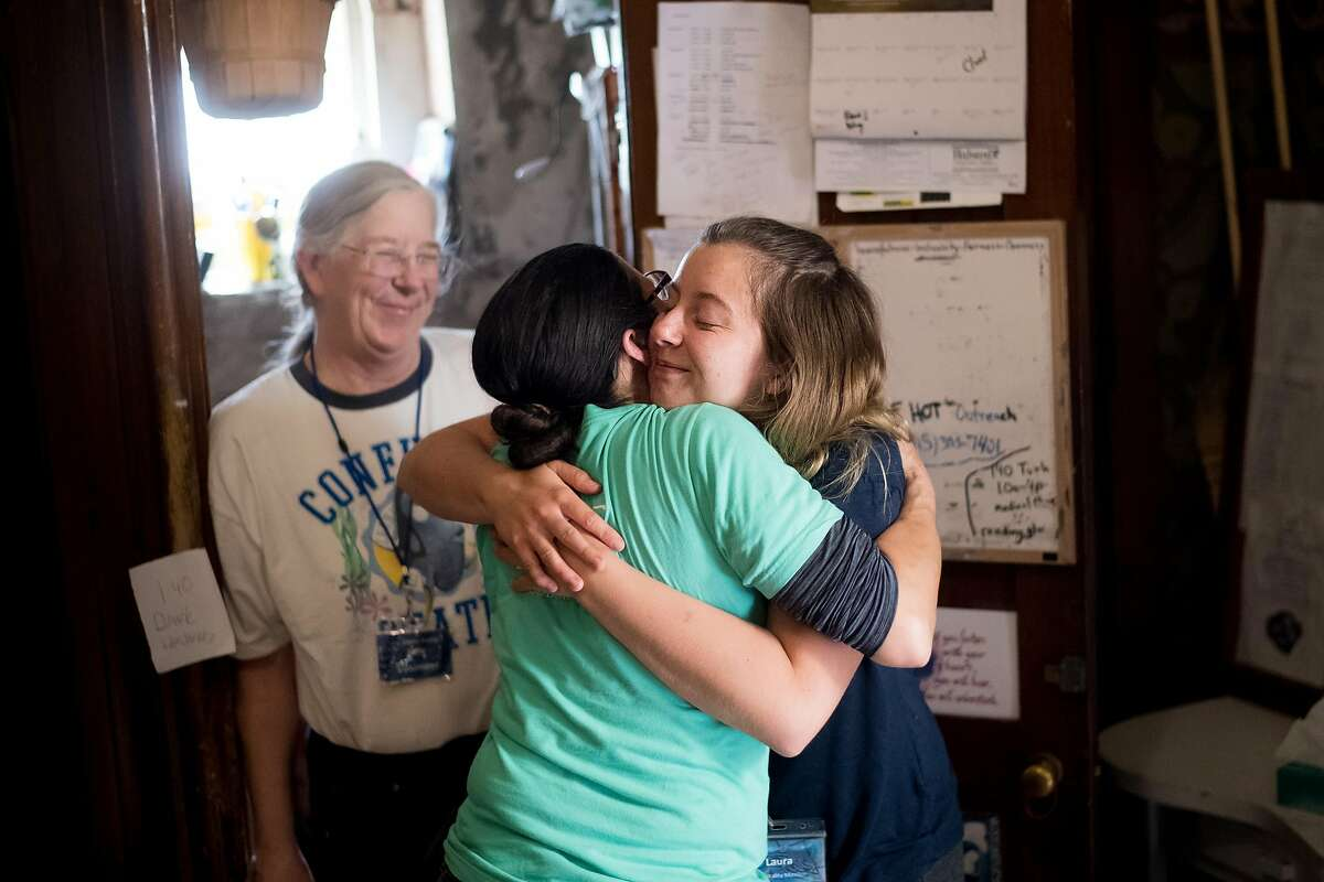 Laura Hassel, a volunteer at St. Boniface Catholic Church, hugs Gubbio Project program manager Tina Christopher on Friday, April 21, 2017, in San Francisco. Hassel was nearby when William Ellis, a homeless man, collapsed and died at the church.