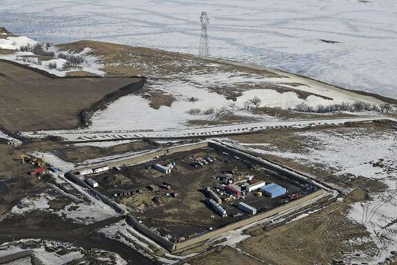 "FILE - In this Feb. 13, 2017, aerial file photo shows the site where the final phase of the Dakota Access pipeline will take place with boring equipment routing the pipeline underground and across Lake Oahe to connect with the existing pipeline in Emmons County near Cannon Ball, N.D. Environmental activists who tried to disrupt some oil pipeline operations in four states to protest the pipeline say they aren't responsible for any recent attacks on that pipeline. Dakota Access developer Energy Transfer Partners said in court documents Monday, March 20, 2017, that there have been ""coordinated physical attacks"" along the $3.8 billion pipeline that will carry oil from North Dakota to Illinois. (Tom Stromme/The Bismarck Tribune via AP, File)"