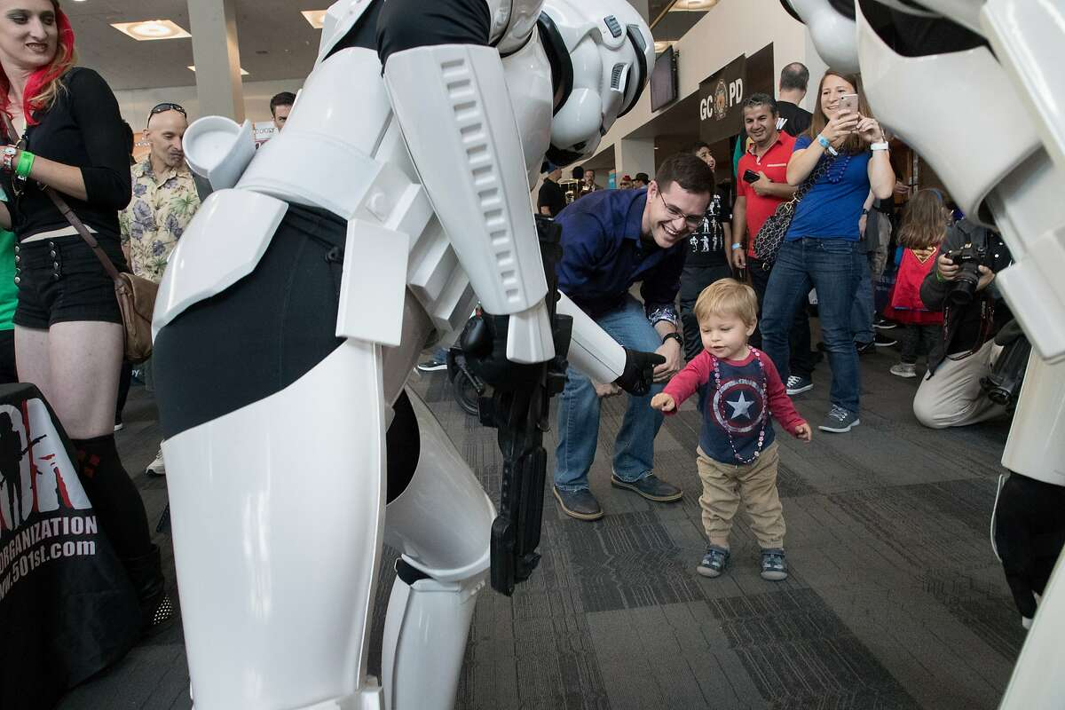 Andrew Bowen, 1.5-years fist pumps with Storm Troopers with dad James and mom Martha taking photos from Monterey at Santa Clara Comic Con on Saturday, April 22, 2017 in San Jose , CA.
