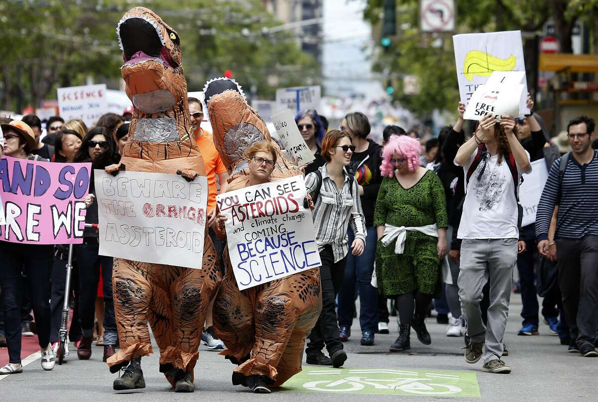 Tim Kingston (left) and Rebecca Hensler dress as dinosaurs for the March for Science on Market Street in San Francisco, Calif. on Saturday, April 22, 2017.