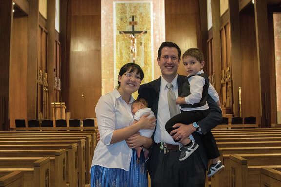 Ashley Hunter holds two-month-old Thomas and her husband, Glenn Hunter, holds two-year-old James after getting married inside of Our Lady of Victory Cathedral in Victoria, Texas.