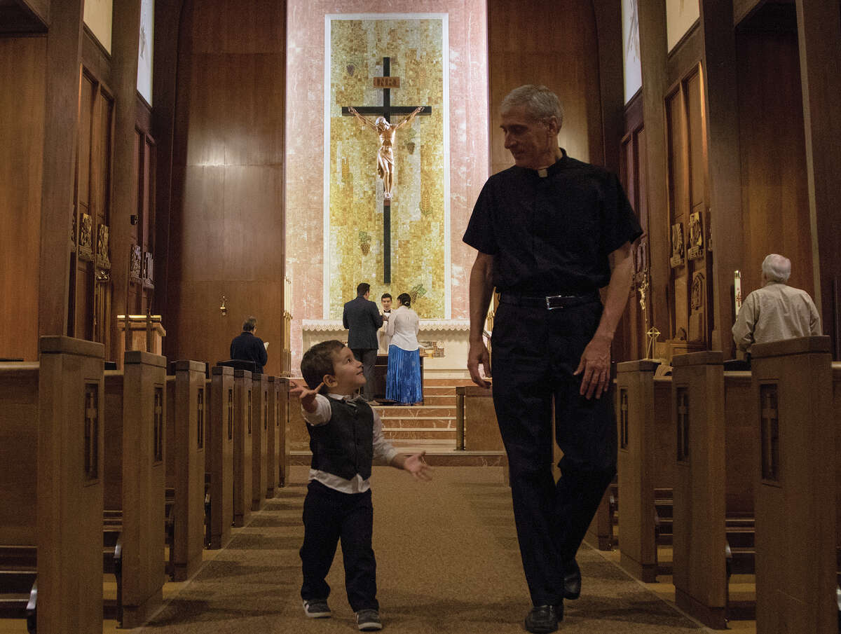 James Hunter, 2, walks down an aisle with Rev. Gary Janak as his parents get married at Our Lady of Victory Cathedral on Thursday, April 13, 2017, in Victoria, Texas.