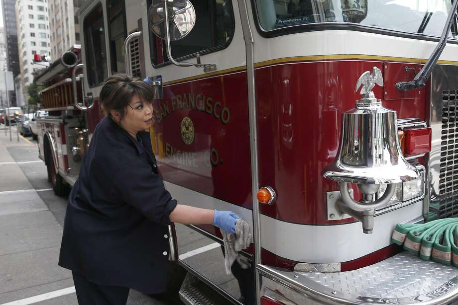 Firefighter Willa Ortega wipes down a fire engine at Station 13 on Sansome Street in S.F. Affordable-housing units would be built above the firehouse under a supervisor's plan. Photo: Paul Chinn, The Chronicle