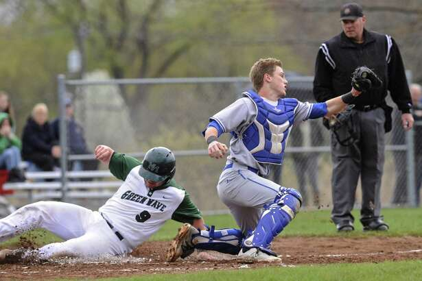 New Milford's Derek Johnson (9) slides safely into home as Newtown catcher Ben Harrison (9) catches the throw in the baseball game between Newtown and New Milford high schools, Saturday, April 22, 2017, at New Milford High School, in New Milford, Conn.