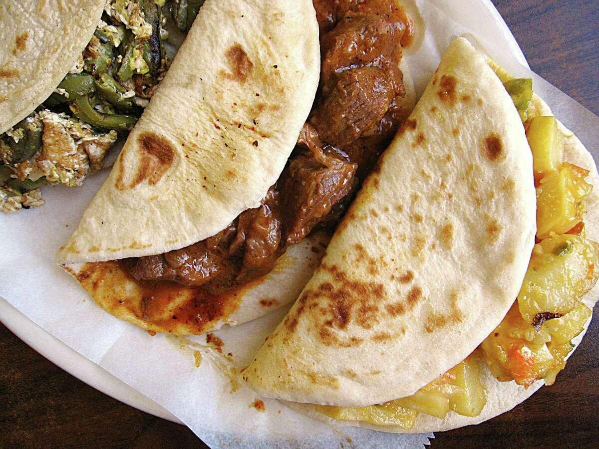 Nopales and egg, left, carne guisada and papas rancheras tacos on handmade tortillas from El Paraiso de Jalisco.
