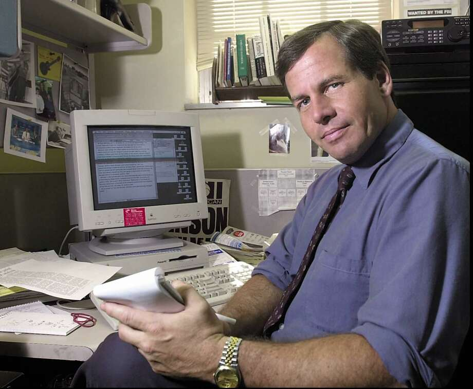 Reporter Joe Johnson poses behind his desk at Greenwich Time in 2001. Photo: Bob Luckey,  Jr., Greenwich Time