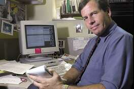 Reporter Joe Johnson poses behind his desk at Greenwich Time in 2001. ..........PHOTO/LUCKEY JR....COLOR