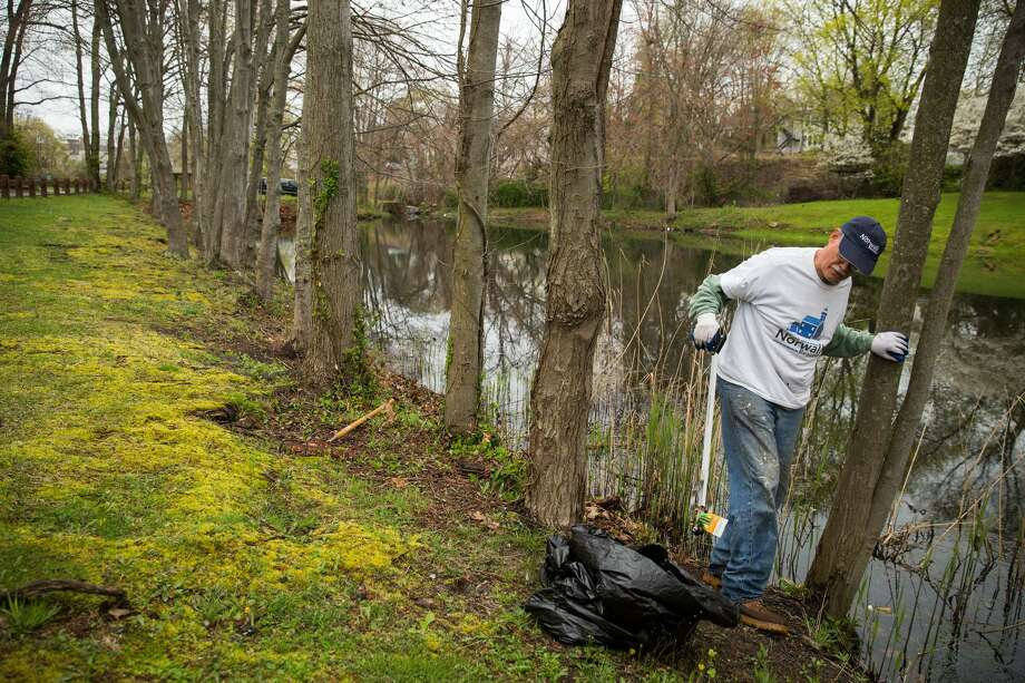Jim del Greco cleans garbage out of the pond at Flax Hill Park during the mayor's annual Earth Day Citywide Spring Cleanup in Norwalk, Conn. on Saturday, April 22, 2016. Photo: Chris Palermo / For Hearst Connecticut Media / Norwalk Hour Freelance