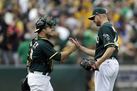 Oakland Athletics' Ryan Madson, right, and Josh Phegley celebrate a win over the Seattle Mariners in a baseball game Saturday, April 22, 2017, in Oakland, Calif. (AP Photo/Ben Margot)
