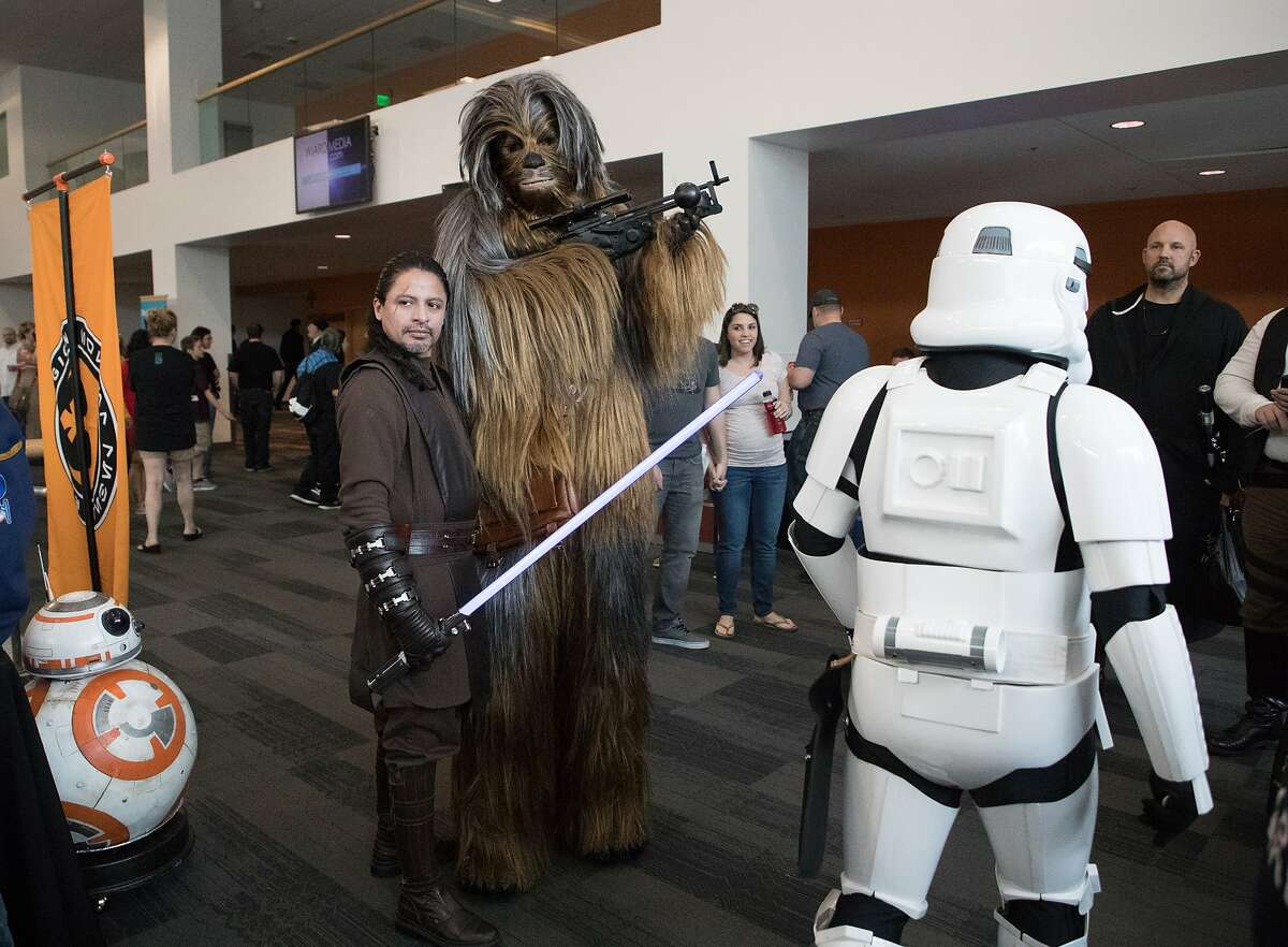 Roberto Moran of SF pose with a Wookie as a Storm Trooper walks by at Silicon Valley Comic Con on Saturday, April 22, 2017 in San Jose , CA.