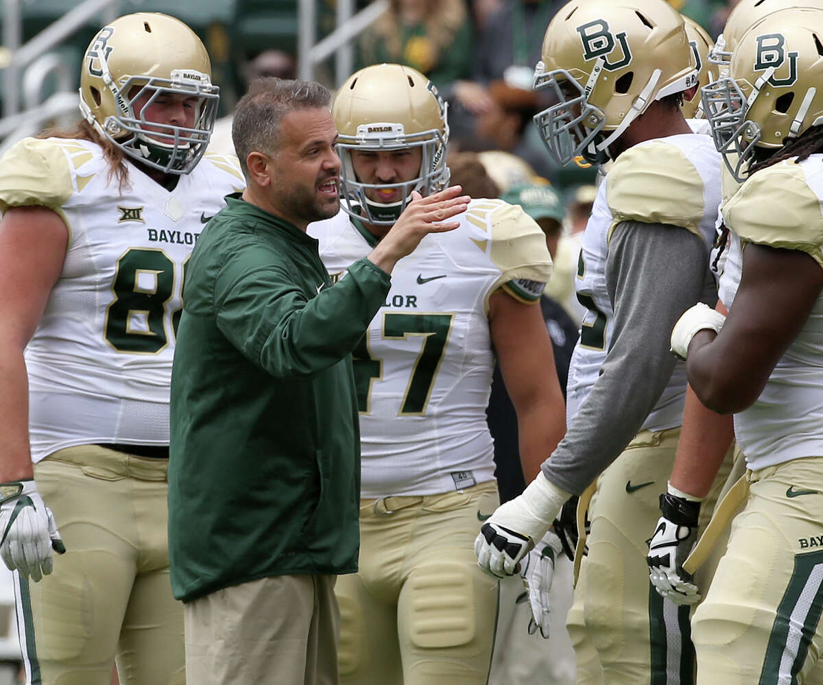 Baylor first-year football coach Matt Rhule offers instruction to several of his offensive players during Saturday's Green and Gold spring game at Waco.