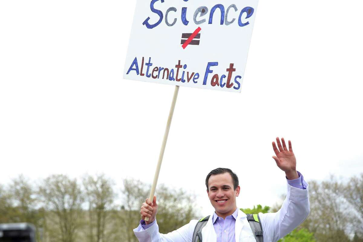 Clinical researcher Derek Salud waves his sign as thousands of demonstrators participate in the March for Science, which traveled through downtown Seattle from Cal Anderson Park to the Seattle Center, April 22, 2017. People in cities around the world spent the day rallying in support of science, truth and facts.