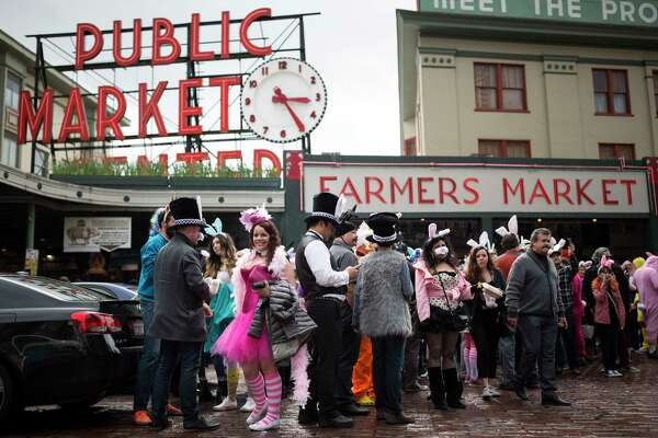 Participants gather at the Pike Place Market sign to take a group photo during the 7th annual BunnyCon bar hop in in Seattle on Saturday, April 22, 2017. Hundreds of bunnies (and some carrots) hopped their way through a dozen downtown Seattle bars during the nearly 15 hour event.