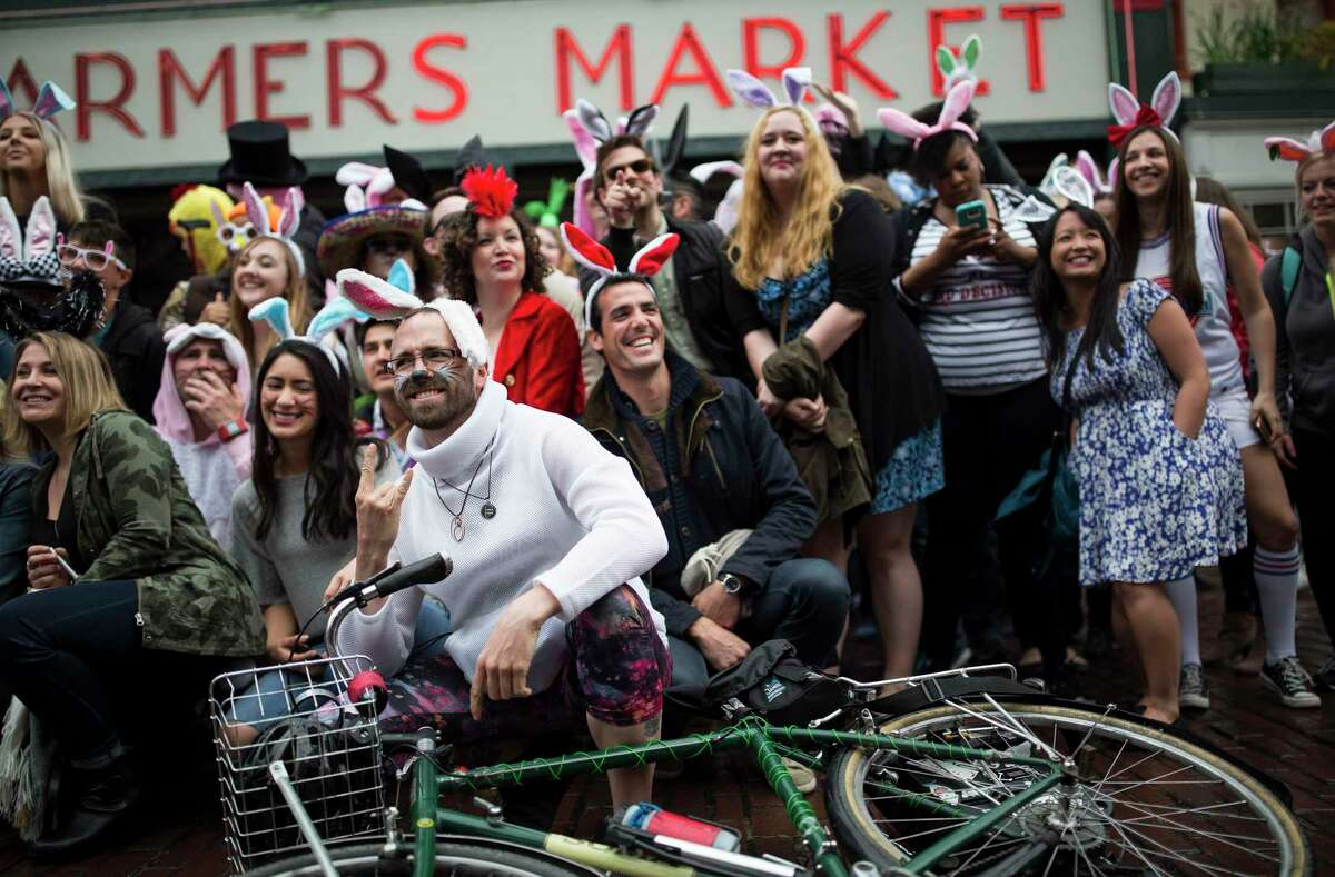A bunny on a bike joins the group photo at the Pike Place Market sign during the 7th annual BunnyCon bar hop in in Seattle on Saturday, April 22, 2017. Hundreds of bunnies (and some carrots) hopped their way through a dozen downtown Seattle bars during the nearly 15 hour event.